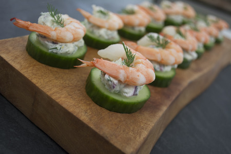 crudite: Shrimp Cucumber and Dill Cream Cheese Round Hor Doeuvres on Wooden Serving Tray