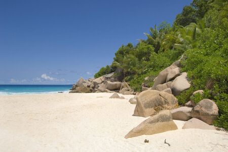 unspoiled: Dramatic unspoiled Grand Anse beach, inviting waters and tropical landscape of La Digue Island, Seychelles