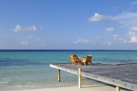 Chairs and table on deck by beach, Kuramathi island, Maldives Stock Photo