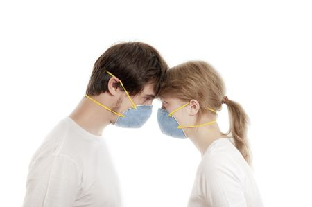 smooching: Man and woman 20-35 years  in blue face masks  with heads together  against white background
