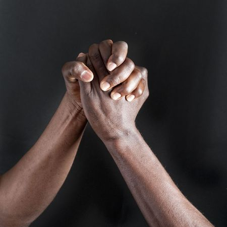 Two adult men shaking hands  close-up against black background