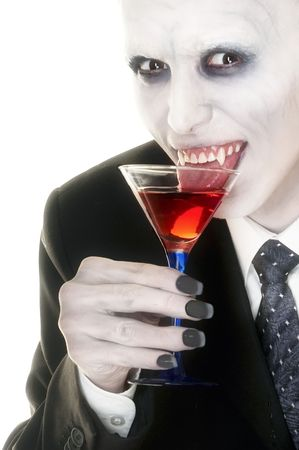 Actor playing vampire drinks red liquid from cocktail glass