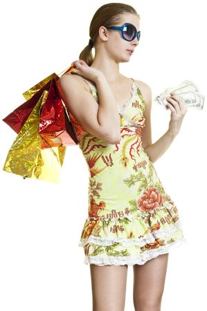 young woman with shopping bags in one  hand and cash in other  on a white background photo