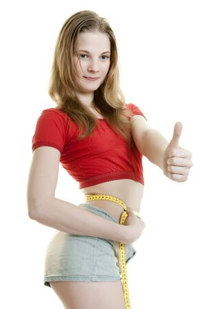Young  slender woman measuring her waist giving thumbs up hand gesture Stock Photo - 6942729