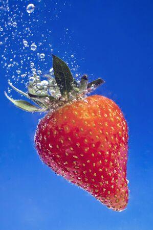 Garden strawberry underwater against blue background photo