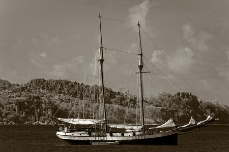 schooner: two-masted schooner anchored  off-shore of Praslin island, Seychelles Stock Photo