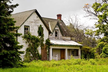 An abandoned, decaying Lock Master's House sits in the overgrowth at the Long Island Locks along the historic Rideau Canal.