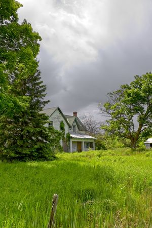 decrepit: An old, abandoned Lockmasters house sits under threatening storm clouds, amidst the dense, neglected overgrowth of the historic Ottawa Valley, Rideau Canal area. Stock Photo