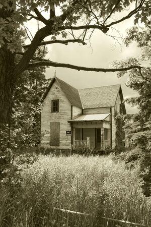 prohibido el paso: Un viejo, la casa abandonada Lockmaster, rodado en un tono sepia, con el signo prohibido el paso. Foto de archivo