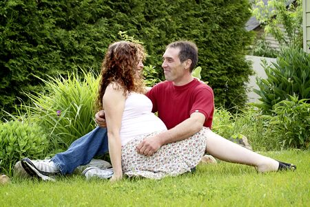 A young, happy, pregnant couple sitting on grass outside.