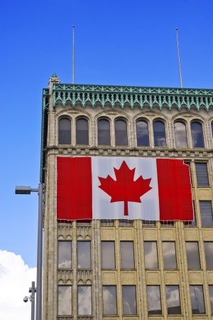 affixed: The exterior of a building with a giant Canadian flag affixed to its side. Stock Photo