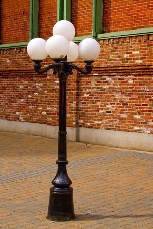 An old-fashioned metal street lamp surrounded by red brick. photo