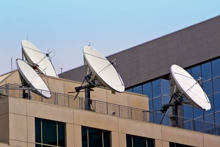 An array of four satellite dishes aimed toward space, on top of a building roof.