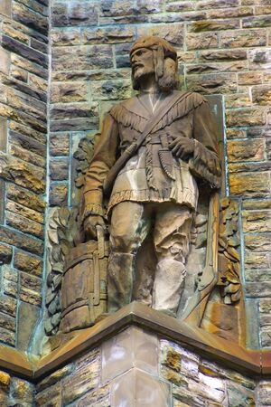 And old, stone statue of a Canadian Voyageur/Frontiersman against an old, stained rock wall.