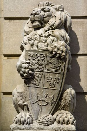A stone statue of a regal lion holding the heraldic shield of Canada in its paws. Standard-Bild