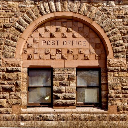 Post Office written atop on old style window.