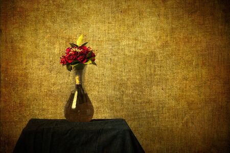 A still-life image of red roses in a vase with texture added in a grunge style and including ample copy space. photo