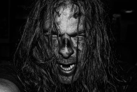 possessed: The face of an evil, male zombie in high-contrast black and white.