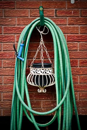 A common home garden hose coiled up and hanging on brick wall with hanging planter underneath.