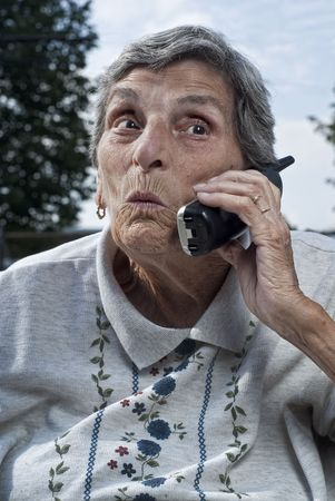 An elderly woman, with a look of surprise on her face, talks on a cordless phone. Standard-Bild
