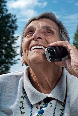 A happy, smiling seior woman enjoys a conversation on a cordless, mobile phone. photo
