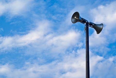 A pair of loudspeaker megaphones mounted atop a tall pole set against a cloudy blue sky.