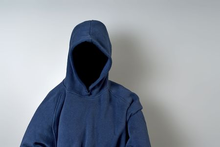 hoody: A blue hoodie with nothing but a dark shadow in place of a face against a white wall with copy-space.