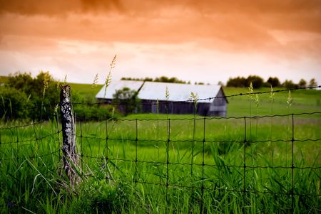 An old, rotting wire fence stands in the foreground with an old barn in the background, under a stormy, orange sky. photo