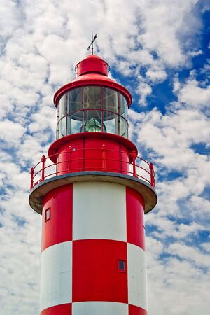 Looking up at an old, red and white historic maritime lighthouse in daytime. Stock Photo - 7579064