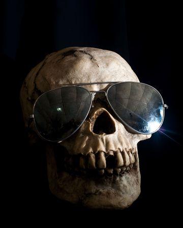Human skull in shadow wearing mirrored aviator sunglasses