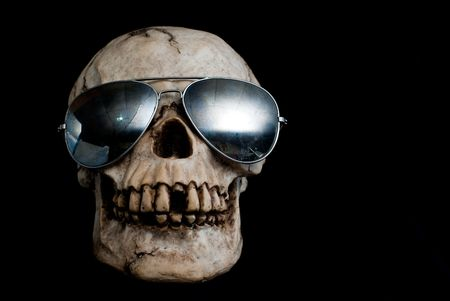 An old, human skull wearing mirrored aviator type sunglasses.