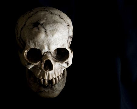 Front-view of an old, cracked and damaged human skull in deep shadow.