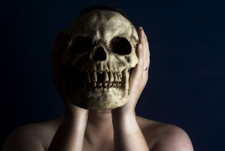A woman holds a human skull in front of her face against a black background.