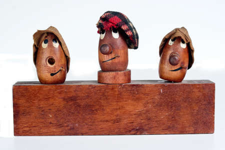 Three caricature like, funny, wooden, human men isolated on white.