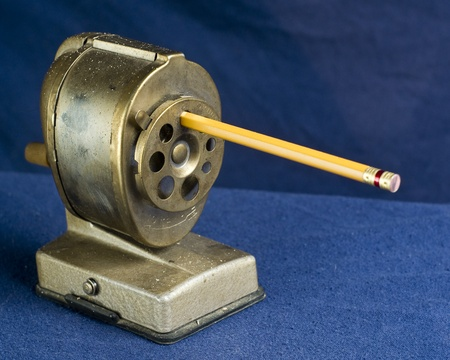 A dirty, antique style pencil sharpener with pencil inserted. Stock Photo - 8669044