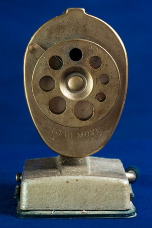 An old, dirty, antique pencil sharpener as seen straight on.
