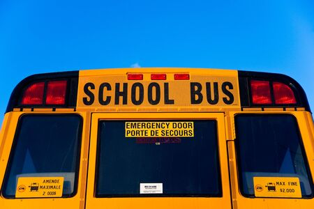 The top half of the back of a yellow School Bus displaying the words