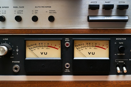 Stereo VU meters on a portion of an old, dirty, vintage, analog reel-to-reel tape deck.