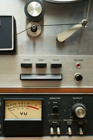 Portion of an old, vintage, and dirty analog reel-to-reel type stereo tape recorder. photo