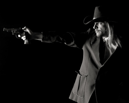 Black and white image of an outlaw character aiming a revolver.
