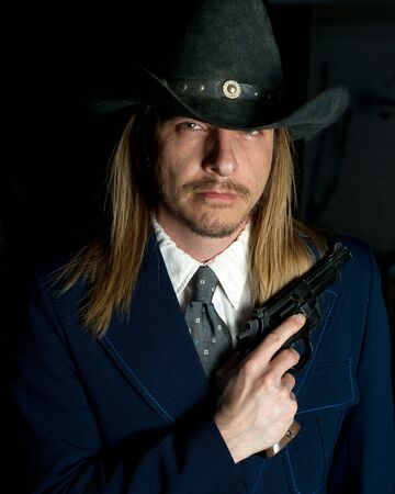 scruffy: A long haired man in cowboy hat holds a revolver.