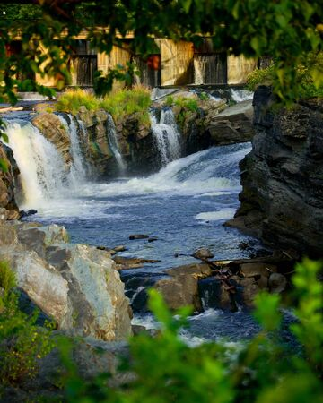 geological: The scenic view through forest trees of Hogs Back waterfalls on the Rideau River in Ottawa, Ontario, Canada Stock Photo