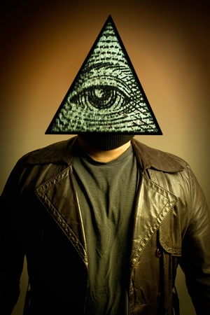 A male figure in a leather trench coat wearing an illuminati symbol eye of providence, or all seeing eye mask.