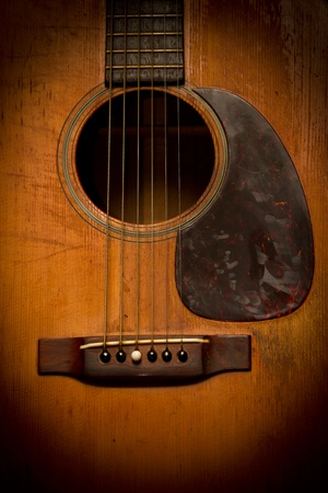 frets: A close-up image of the sound hole, strings and bridge of a very old, vintage, scratched and beat-up acoustic guitar. Stock Photo