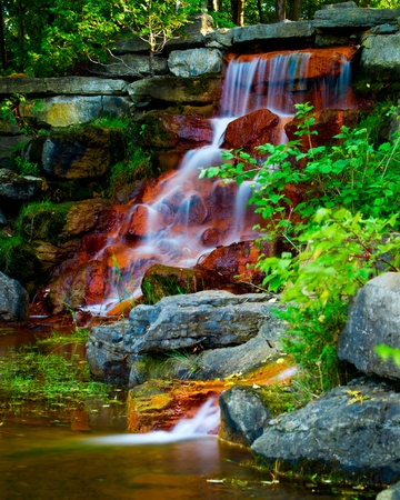 cascade: Water cascades over the red algae covered rock of a beautiful man-made waterfall in Andrew Haydon park in Ottawa, Ontario Canada.