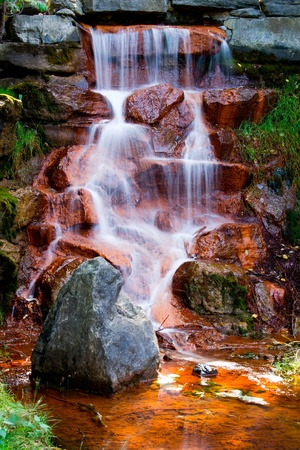 The cascading waters of a beautiful waterfall flow down over red algae covered stones in Andrew Haydon Park in Ottawa, Ontario Canada
