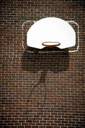 茶色、レンガの壁に貼られたないネットと白の背板のバスケット ボールのフープ。