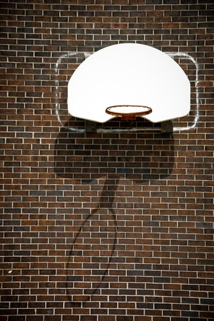 A basketball hoop with no net and white backboard affixed to a brown, brick wall.