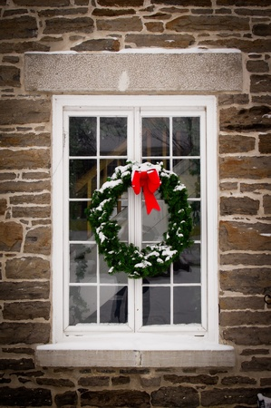 window pane: A green spruce Christmas wreath with red ribbon hangs in the middle of an old, snow covered window pane set in stone wall.