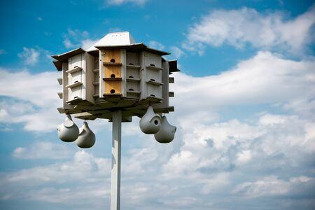 A wooden bird condo (large bird house) set against a cloudy blue sky. photo
